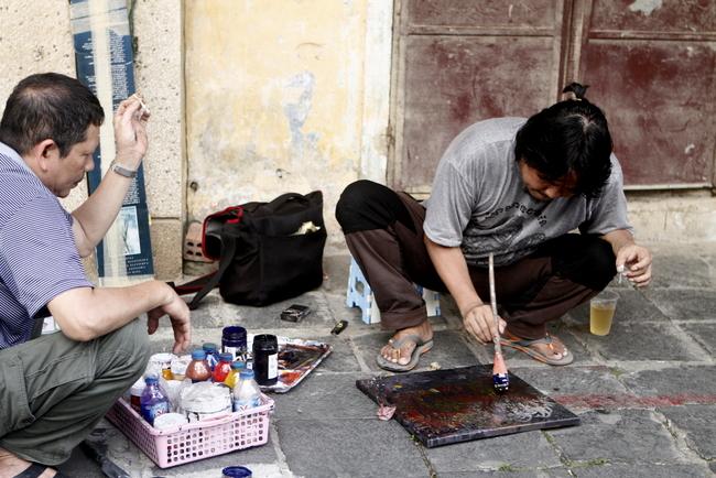 Trong một con phố khác, người thợ đang vẽ lại bảng hiệu cho một chủ nhà, chuẩn bị mở lại cửa hàng trong tháng 5 này.