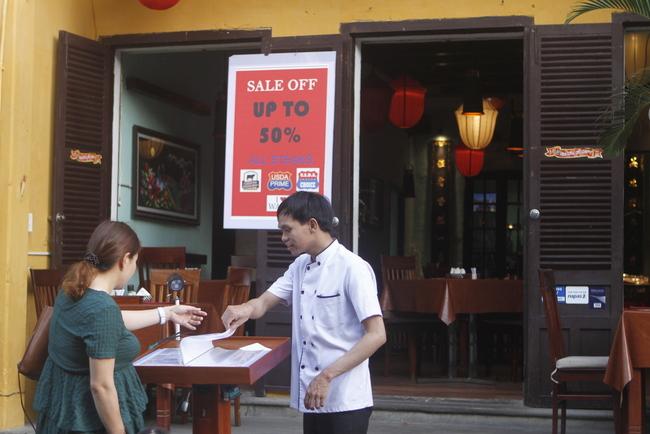 Các quán cà phê, nhà hàng đã mở cửa trở lại, nhưng thưa thớt khách. Trong ảnh là đầu bếp một nhà hàng trực tiếp ra giới thiệu món cho khách ngang qua.