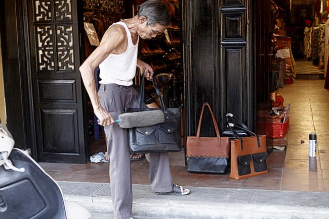 Người đàn ông này đang phủi bụi túi xách ở cửa hàng của nhà mình, mới mở lại trong dịp lễ.